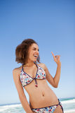 Young attractive woman standing on the beach while pointing her. Young woman standing on the beach while pointing her finger up with a smile Stock Photo