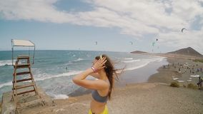 Young attractive woman standing on the coast by the sea in windy day. Place for kitesurfing on a background stock video footage