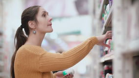 Young attractive woman standing in front of shelves with deodorant, holding two and try to choose. 4K stock video