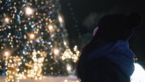 Young Attractive Woman Standing In Front of Shiny Christmas Tree. Woman In Warm Clothes Outside At Night Looking At
