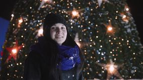 Young attractive woman standing in front of shiny christmas tree. woman in warm clothes outside at night looking at. Camera And Smiling. Holiday And Lifestyle stock video footage