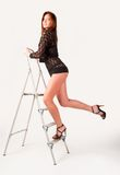 Pretty brunette girl standing on ladder Royalty Free Stock Photo