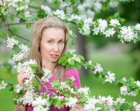 Apple-tree garden in the spring and young woman the blonde among trees Royalty Free Stock Images