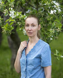Young attractive woman standing near the blossoming apple tree Stock Images