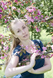 Young attractive woman standing near the blossoming crimson apple tree Royalty Free Stock Images