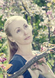 Young attractive woman standing near the blossoming crimson apple tree, toning Royalty Free Stock Photography