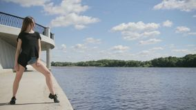 Young attractive woman standing near the river stock footage