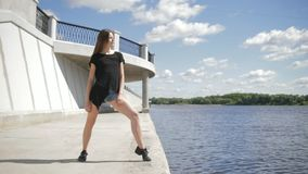 Young attractive woman standing near the river stock video