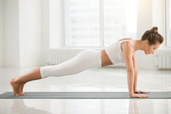Young attractive woman standing in Plank pose, white color backg Stock Photos
