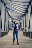 Young and attractive woman is standing with raised up hands on the bridge. Royalty Free Stock Photography