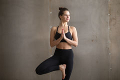 Young attractive woman standing in Tree pose, grey studio backgr. Portrait of young smiling attractive yogi woman practicing yoga, standing in Vrksasana exercise Stock Photo