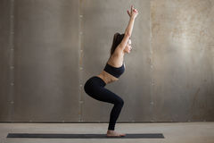 Young attractive woman standing in Utkatasana pose, grey studio Stock Photography