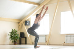 Young attractive woman standing in Utkatasana pose, home interio. Young attractive happy woman practicing yoga, standing in Utkatasana exercise, Chair pose Royalty Free Stock Photos