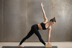 Young attractive woman standing in Utthita Trikonasana pose with. Young attractive yogi woman in black practicing yoga, standing in Utthita Trikonasana exercise Stock Images