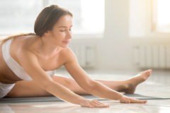 Young attractive woman in Straight Angle pose, white color backg. Young attractive yogi woman practicing yoga, doing Upavistha Konasana exercise, Wide Angle stock photo