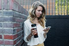 Young attractive woman at park, working with phone, drinking coffee, having lunch in a hurry. Business concept photo Stock Photo