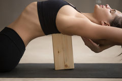 Young attractive woman stretching in Matsyasana pose with block, stock photography