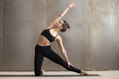 Young attractive woman stretching in Parighasana pose, grey stud Stock Image