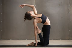 Young attractive woman stretching in Ustrasana pose, grey studio Stock Photo