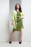 Young attractive woman in striped dress and coat Stock Image
