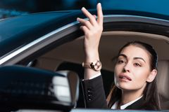 Young attractive woman in suit calling someone while sitting in drivers seat of. Passenger car Stock Image