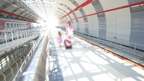 Young attractive woman with suitcase and her pretty daughter at the railway station go to the train stock footage