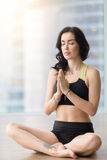 Young attractive woman in Sukhasana pose against sunny floor win Stock Photo