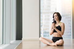 Young attractive woman in Sukhasana pose near the floor windows Royalty Free Stock Photos