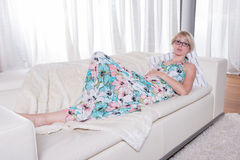 Young attractive woman in summer dress is relaxing on the couch Royalty Free Stock Image