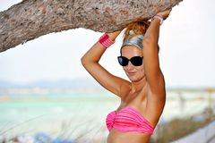 Young attractive woman in sunglasses and bikini under tree brach in summer vacation Stock Photos
