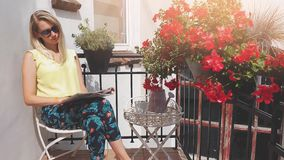 Young attractive woman with sunglasses enjoying sun and reading magazine on romantic balcony with flower boxes stock video footage