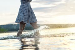 Young attractive woman in sunset. Water splashing when walking. Young attractive woman in sunset. Water splashing when walking in the lake. Carefree and happy stock photos