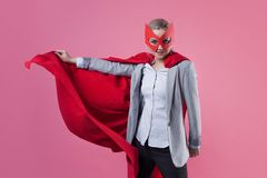 Young attractive woman superhero. Girl in a business suit and a mask with red cloak of hero. stock image