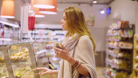 Young attractive woman in a supermarket Royalty Free Stock Images