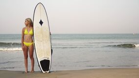 Young attractive woman surfer in a swimsuit with a surfboard on the beach