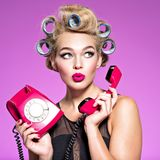 Young attractive woman surprised after talking on the phone. Girl with blue curlers excited after phone call by a retro phone royalty free stock images