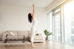 Young attractive woman in Tadasana pose, cozy hotel living room Stock Images