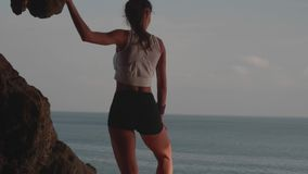 Woman taking break after morning jogging on sea shore cliff at sunrise. Young attractive woman taking break after morning jogging on sea shore cliff at sunrise stock video