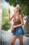 Young attractive woman talking on a cell phone in a street Royalty Free Stock Image