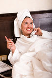 Young attractive woman talking on phone in bed Royalty Free Stock Photography