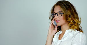 Young attractive woman talks on telephone and moves her gaze, reflections on her glasses. stock footage
