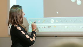 Young attractive woman tells a class lecture on the background of a smart board. The projector displays the molecule