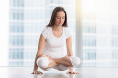 Young attractive woman in Tolasana pose against floor window stock images
