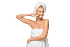 Young attractive woman in towel brushing her teeth with toothbrush Stock Photography