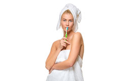 Young attractive woman in towel brushing her teeth with toothbrush Stock Photos