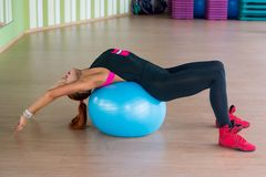 Young attractive woman trains on the ball in fitness near in the Stock Images