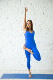Young attractive woman in Tree pose, white studio background Stock Photos