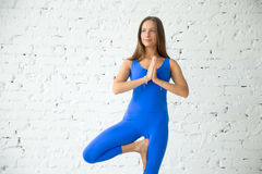 Young attractive woman in Tree pose, white studio background. Portrait of young attractive smiling woman practicing yoga, standing in Vrksasana exercise, Tree Royalty Free Stock Photo