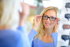 Young attractive woman trying glasses at optician Stock Images