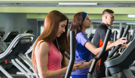 Young attractive woman turning on music while exercising. Young attractive women turning on music while exercising on the crosstrainer machines in fitness center Royalty Free Stock Photography